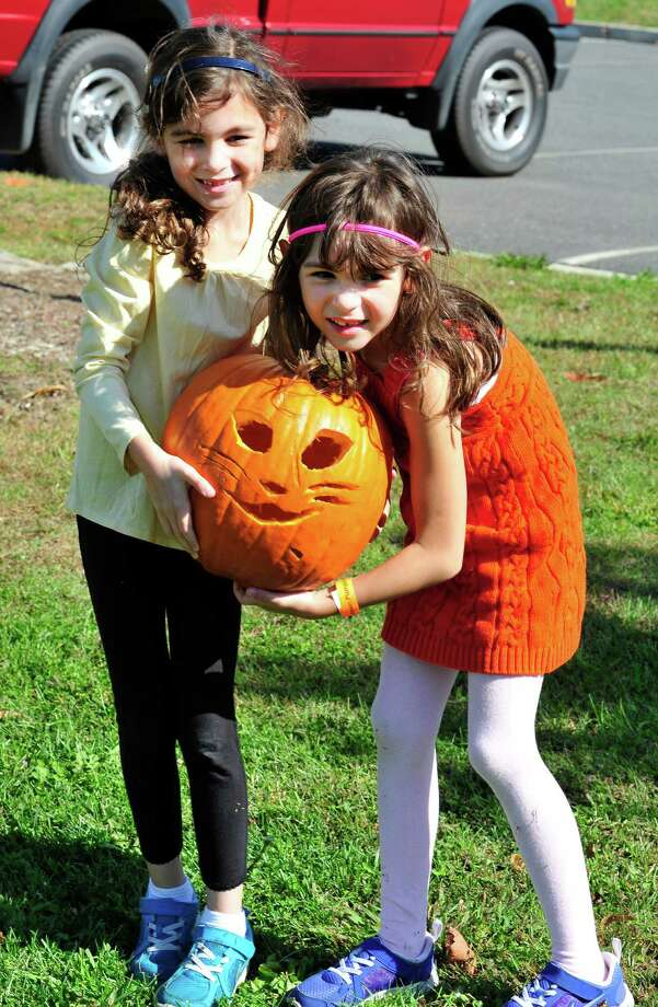 Ava Baroody, 7, left, and her sister, Sophia, 5, hold their pumpkin at the Newtown Pumpkin Festival on the Fairfield Hills Campus in Newtown, Conn. Saturday, Oct. 12, 2013. Photo: Michael Duffy / The News-Times