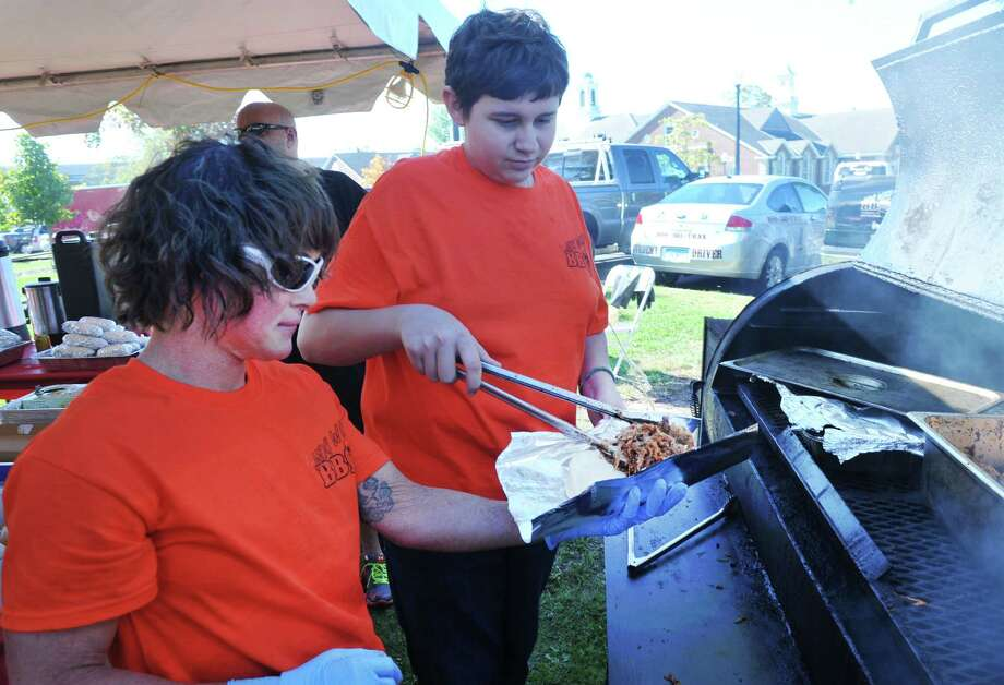 Katie Brunetti holds a plate of pulled pork that her nephew, Hunter Brunetti, 14, servrs from the grill at the Newtown Pumpkin Festival on the Fairfield Hills Campus in Newtown, Conn. Saturday, Oct. 12, 2013. Photo: Michael Duffy / The News-Times