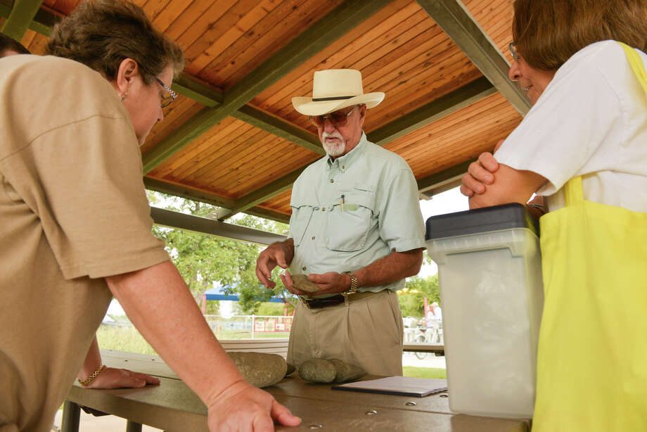 Harry Shafer, Curator of Artifacts at the Witte Museum, looks over items for Marybeth Tomka (left) and Grace Keyes (right) during the city's Artifacts Identification Day at Padre park on Saturday. Photo: Robin Jerstad