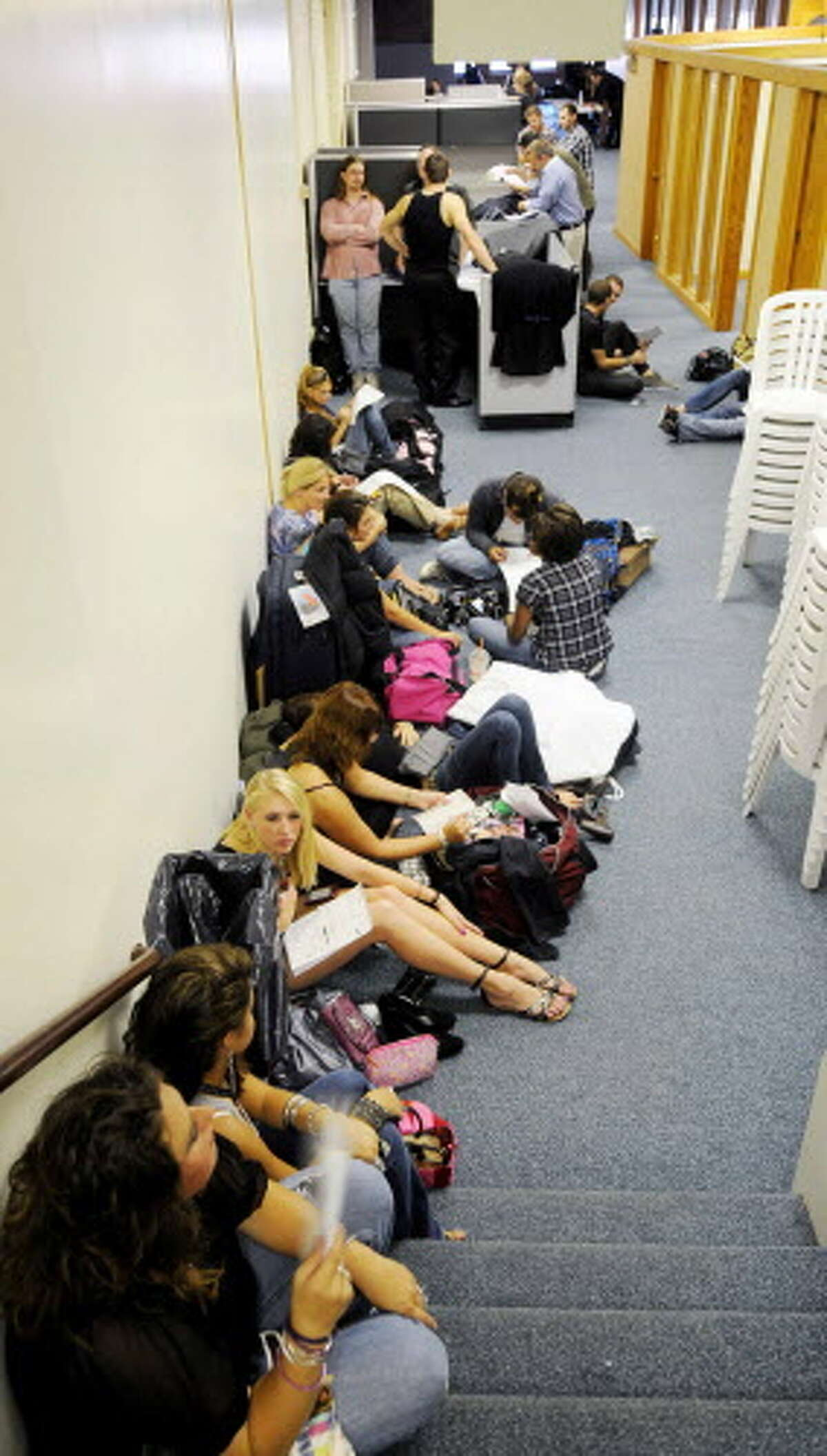 Extras fill out their paperwork and wait in a holding room in the Steuben Athletic Club after they were cast for a scene in the independent film