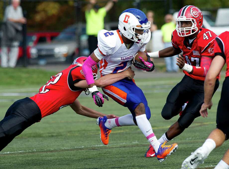 Danbury's Elijah Duffy carries the ball during Saturday's football game at New Canaan High School on October 12, 2013. Photo: Lindsay Perry / Stamford Advocate
