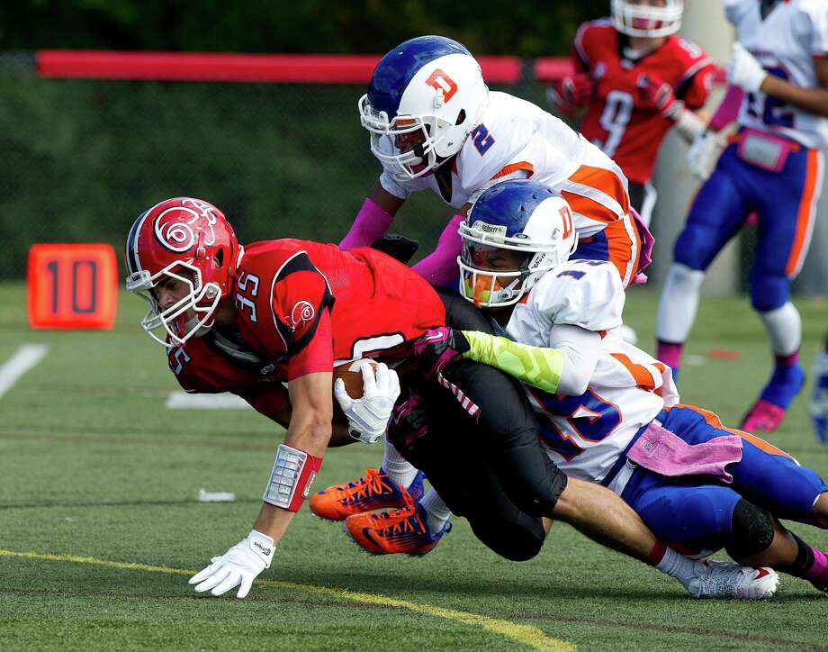 New Canaan's Seth Neeleman is tackled during Saturday's football game at New Canaan High School on October 12, 2013. Photo: Lindsay Perry / Stamford Advocate