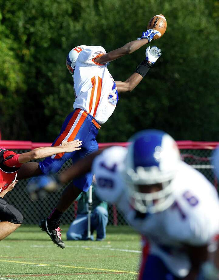 Danbury's Pierre Moudourou dives for a pass that falls incomplete during Saturday's football game at New Canaan High School on October 12, 2013. Photo: Lindsay Perry / Stamford Advocate