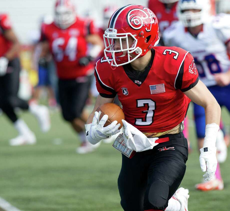 New Canaan's Jack Gilio carries the ball during Saturday's football game at New Canaan High School on October 12, 2013. Photo: Lindsay Perry / Stamford Advocate