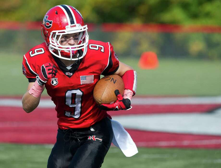 New Canaan's Cole Turpin carries the ball during Saturday's football game at New Canaan High School on October 12, 2013. Photo: Lindsay Perry / Stamford Advocate
