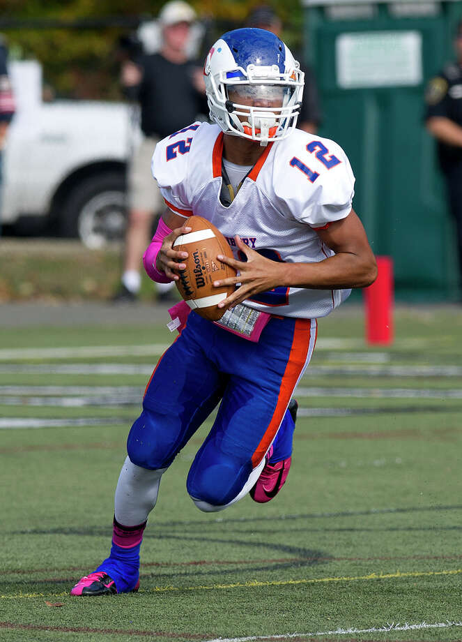 Danbury's Anferny Ith carries the ball during Saturday's football game at New Canaan High School on October 12, 2013. Photo: Lindsay Perry / Stamford Advocate