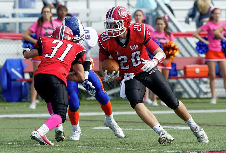 New Canaan's Kyle Smith carries the ball during Saturday's football game at New Canaan High School on October 12, 2013. Photo: Lindsay Perry / Stamford Advocate
