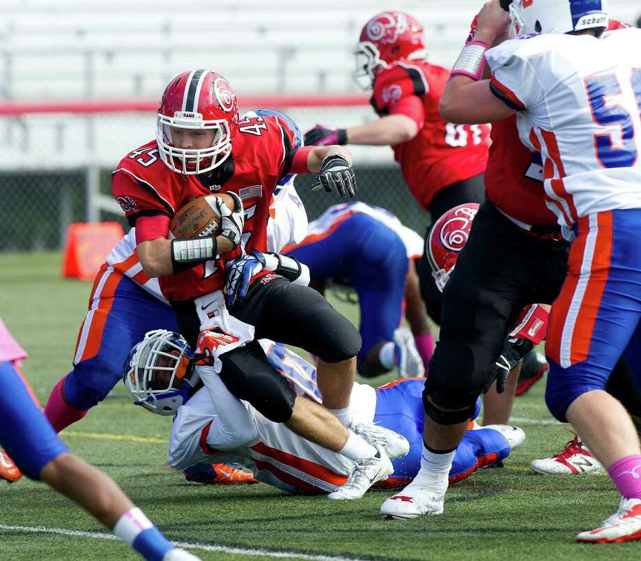 New Canaan's Morgan Carson carries the ball during Saturday's football game at New Canaan High School on October 12, 2013. Photo: Lindsay Perry / Stamford Advocate
