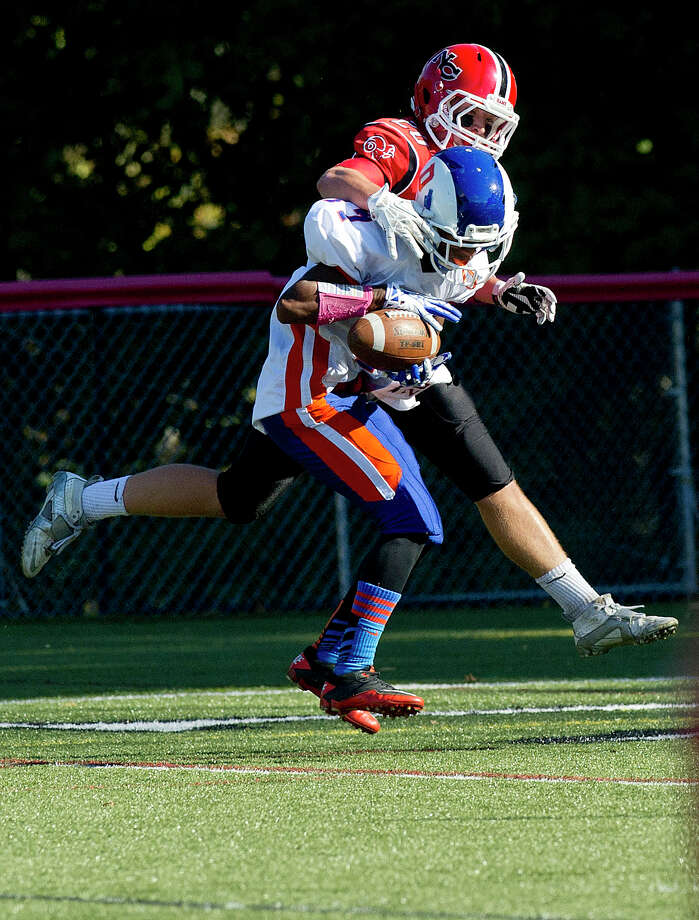 A pass intended for New Canaan's Kyle Smith is intercepted by Danbury's Matthew Andrew during Saturday's football game at New Canaan High School on October 12, 2013. Photo: Lindsay Perry / Stamford Advocate