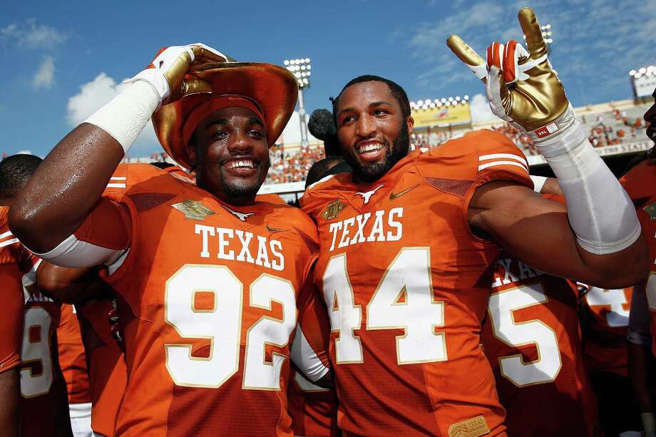 DALLAS, TX - OCTOBER 12:  (L-R) Reggie Wilson #92 of the Texas Longhorns and Jackson Jeffcoat #44 of the Texas Longhorns celebrate with the game trophy after the Longhorns beat the Sooners 36-20 at the Cotton Bowl on October 12, 2013 in Dallas, Texas. Photo: Tom Pennington, Getty Images / 2013 Getty Images
