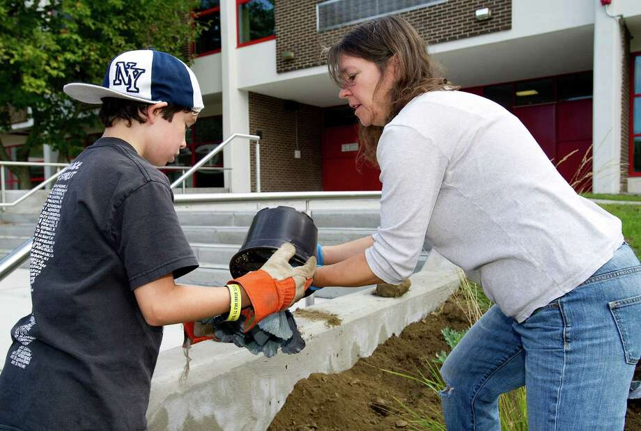 Nick Donohue, 12, left, and Irene Eddy, right, plant a purple cabbage during a clean-up at Turn of River Middle School in Stamford, Conn., on Saturday, October 12, 2013, to prepare the courtyard for a dedication to Carol Pavia, who worked in the office at the school and died in 2012. Photo: Lindsay Perry / Stamford Advocate