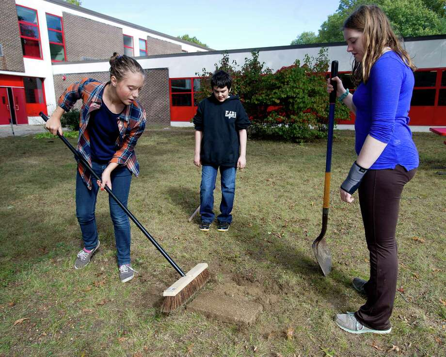 From left, Arden Lesoravage, 13, marco Alvarado, 13, and Grace Lewis, 12, help during a clean-up at Turn of River Middle School in Stamford, Conn., on Saturday, October 12, 2013, to prepare the courtyard for a dedication to Carol Pavia, who worked in the office at the school and died in 2012. Photo: Lindsay Perry / Stamford Advocate