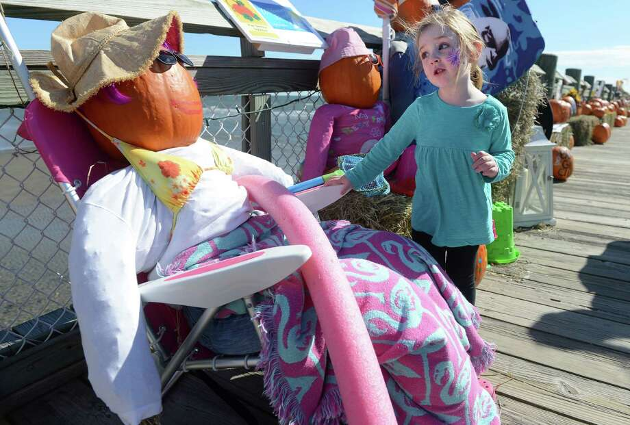 Sophia Skoczolek, 3, of West Haven, checks out a surf-ready pumpkin on display during the Boys and Girls Club of Milford's Pumpkins on the Pier fall festival Saturday, Oct. 12, 2013 at Walnut Beach in Milford, Conn. Photo: Autumn Driscoll / Connecticut Post