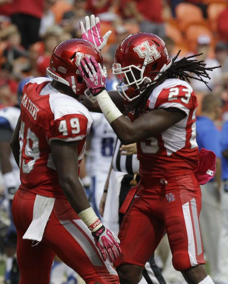 Derrick Mathews (49), left, celebrates with teammate Trevon Stewart, right, after recovering a fumble. Photo:  Melissa Phillip, Houston Chronicle