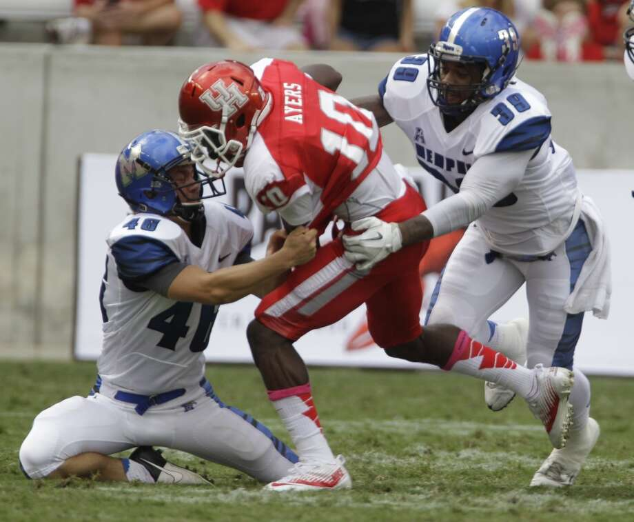 Memphis' Jake Elliott, left, and Reggis Ball, right, work to bring down Demarcus Ayers during the first quarter. Photo:  Melissa Phillip, Houston Chronicle