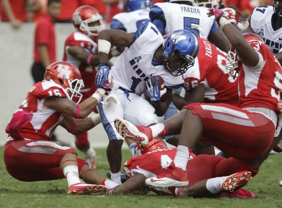 Marquis Warford is stopped by Cougars defenders during the third quarter. Photo: Melissa Phillip, Houston Chronicle