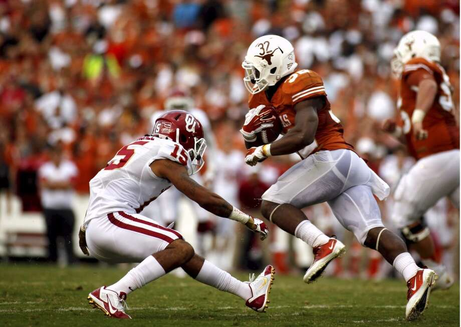 Johnathan Gray (32) runs the ball against Oklahoma during the first half. Photo: Chelsea Purgahn, Associated Press