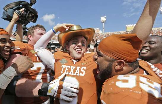 Texas quarterback Case McCoy (6) dons the golden hat trophy as he celebrates with teammate including Desmond Jackson (99). Photo: LM Otero, Associated Press