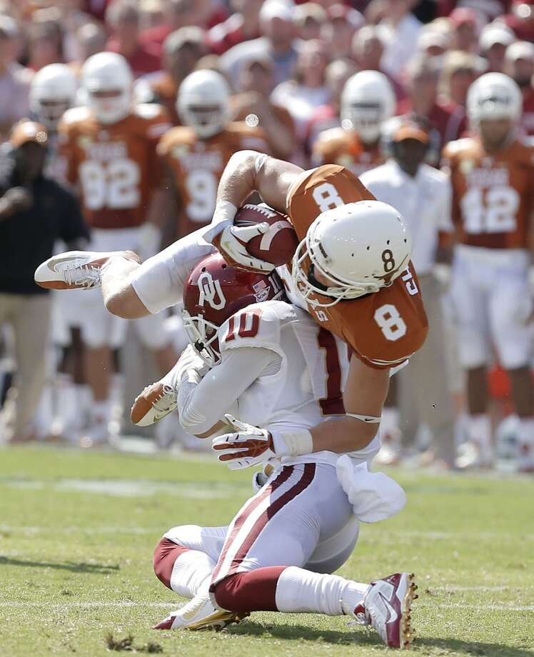 Texas wide receiver Jaxon Shipley (8) is tackled by Oklahoma defensive back Quentin Hayes (10) after a catch during the first half. Photo: Brandon Wade, Associated Press