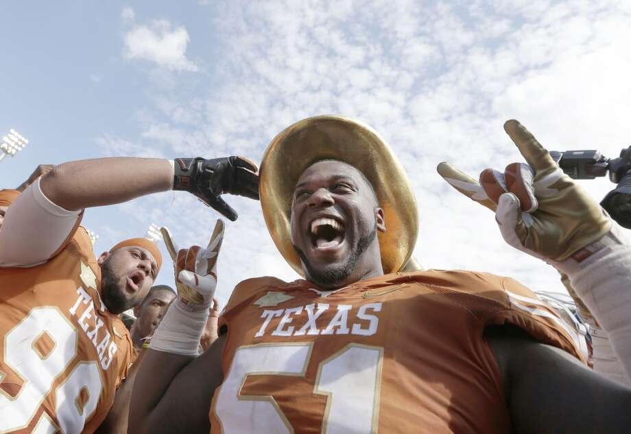 Texas offensive tackle Donald Hawkins (51) dons the Golden Hat and celebrates with teammate defensive tackle Desmond Jackson. Photo: LM Otero, Associated Press