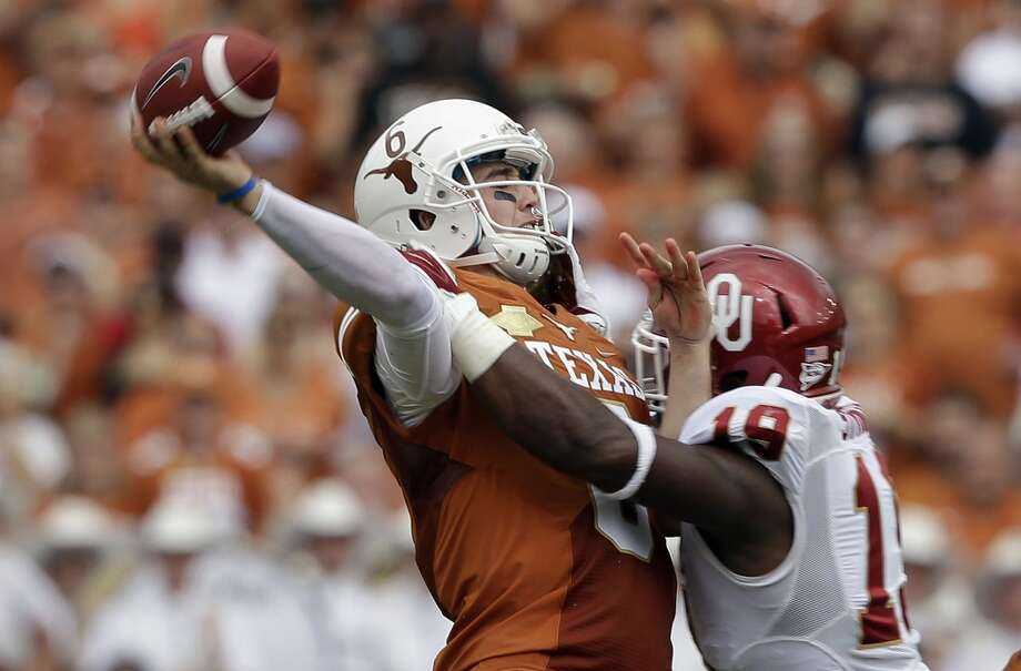 Texas quarterback Case McCoy (6) passes as he his hit by Oklahoma linebacker Eric Striker (19) during the first half. Photo: LM Otero, Associated Press