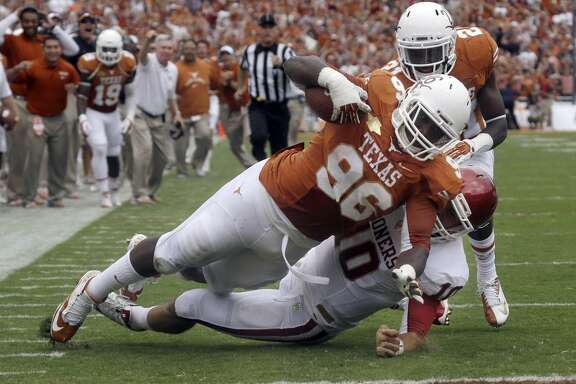 Texas defensive tackle Chris Whaley (96) scores a touchdown after intercepting a pass against Oklahoma quarterback Blake Bell (10) during the first half.
