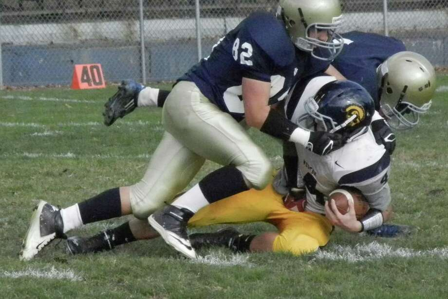 Notre Dame-Fairfield freshman Antonio Addorisio (82) tackles Weston's Alex Frubeis with the help of a teammate in the Lancers' 62-32 loss to at McCarty Stadium in Fairfield in a SWC football game on Saturday, Oct. 12. Photo: Reid L. Walmark / Fairfield Citizen