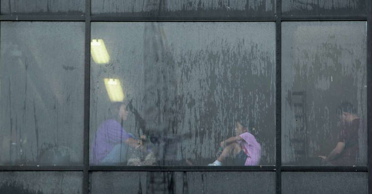 People sit inside a building at the University of St. Thomas during a rain shower at the 35th Houston Italian Festival Saturday, Oct. 12, 2013, in Houston.