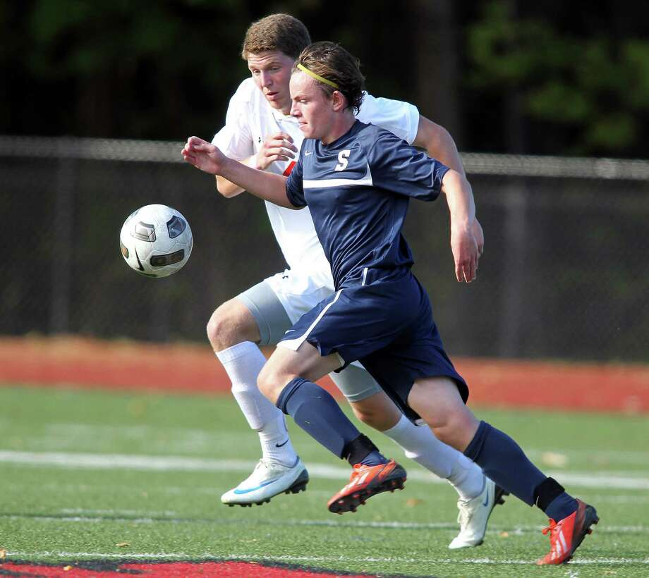 Staples soccer player Charles Leonard gives chase to a loose ball while Greenwich defender Will Gittings defends. The Cardinals, led by a strong offensive showing, won the game, 4-1. © J. Gregory Raymond for The Greenwich Time Photo: J. Gregory Raymond / Stamford Advocate Freelance;  © J. Gregory Raymond
