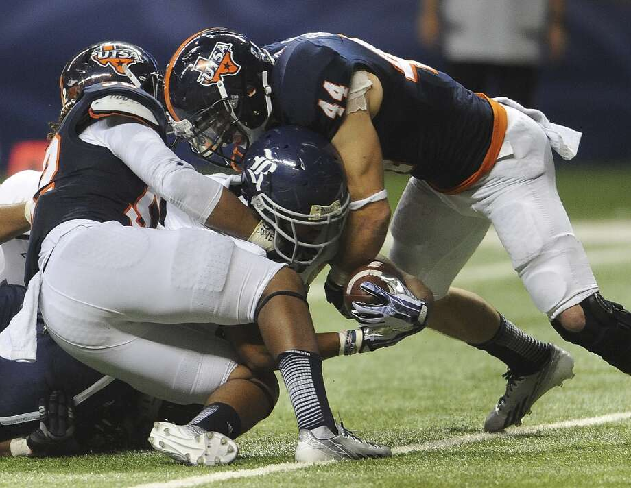 Rice running back Darik Dillard crosses the plane of the goal for a first-half touchdown as UTSA's Steven Kurfehs (44) and Blake Terry attempt to stop him during Conference USA football action in the Alamodome on Saturday, Oct. 12, 2013. Photo: San Antonio Express-News