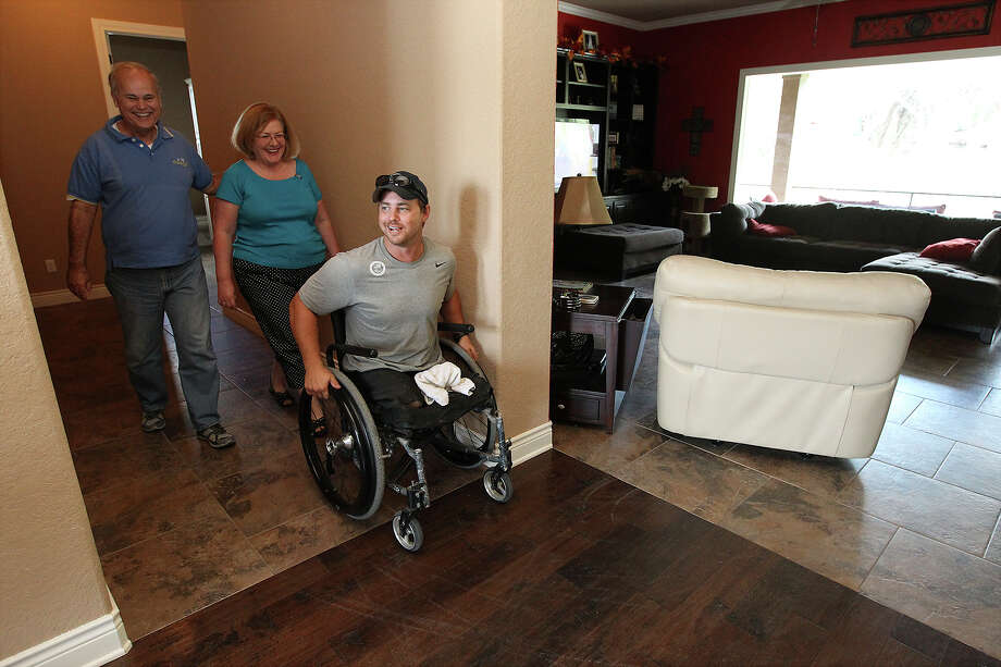 Dave and Katherine Mulhollanddonated two lots to Helping a Hero; unbeknownst to them, the Houston charity had just built a home around the corner from their lots for Kyle Malin, who moved in last October with his wife, Alicia. Now, Helping a Hero will build two more homes for disabled soldiers like Malin, creating a hub for a wounded warrior community in the New Braunfels area. Photo: Kin Man Hui, Staff / ©2013 San Antonio Express-News