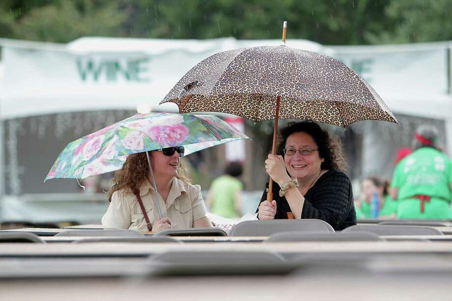 Lettie Schwarz left, and her sister Maria Childress take cover under umbrellas during a rain shower at the 35th Houston Italian Festival at the University of St. Thomas Saturday, Oct. 12, 2013, in Houston. Photo: James Nielsen, Houston Chronicle / © 2013  Houston Chronicle