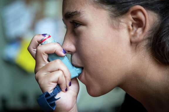 Hannah Hayes, 13, uses an asthma inhaler at her family's vacation home in Truckee, Calif., last month. The high price of commonly used medications for conditions like asthma contributes heavily to health care costs.