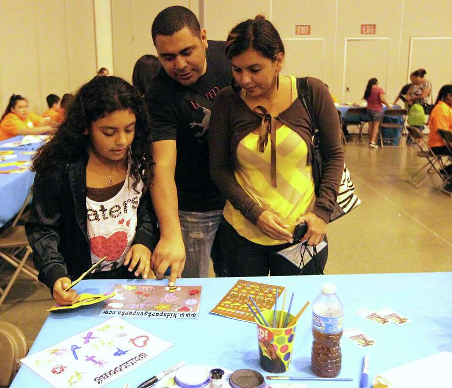 Juliette Cruz, left, and her father Manolo Cruz, center, and mother Jenny Bello, right, at the Be Covered Houston Care Fair. Photo: James Nielsen, Houston Chronicle / © 2013  Houston Chronicle