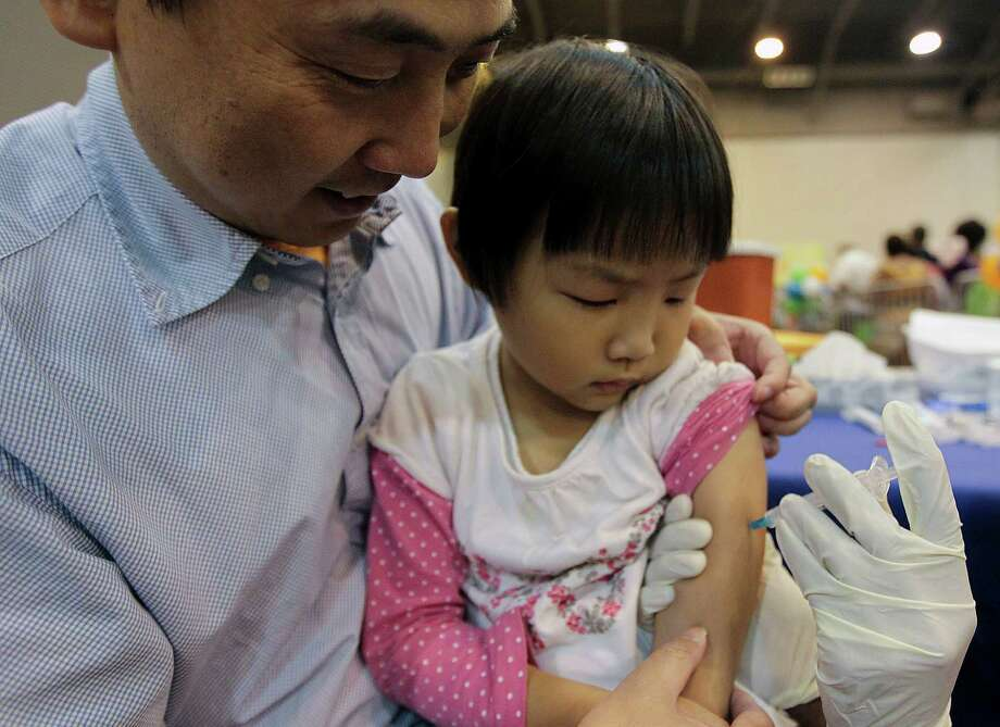 Xiang Li, left, holds his 4-year-old daughter Allison Li as she receives a flu shot at the Be Covered Houston Care Fair. Photo: James Nielsen, Houston Chronicle / © 2013  Houston Chronicle
