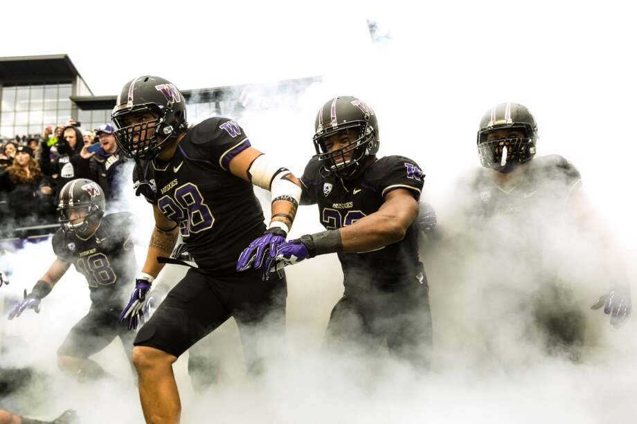 UW Huskies sprint through smoke onto the field before a game against the Oregon Ducks Saturday, Oct. 12, 2013, at Husky Stadium in Seattle. Ducks led the Huskies 21-7 at the half. The Oregon Ducks stand at 5-0 against the Washington Huskies, 4-1, so far in the season to date. (Jordan Stead, seattlepi.com) Photo: JORDAN STEAD, SEATTLEPI.COM
