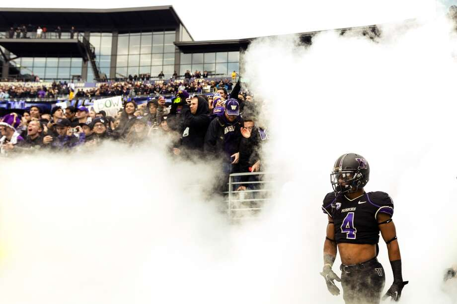 UW Husky Jaydon Mickens, right, walks through smoke onto the field before a game against the Oregon Ducks Saturday, Oct. 12, 2013, at Husky Stadium in Seattle. Ducks led the Huskies 21-7 at the half. The Oregon Ducks stand at 5-0 against the Washington Huskies, 4-1, so far in the season to date. (Jordan Stead, seattlepi.com) Photo: JORDAN STEAD, SEATTLEPI.COM