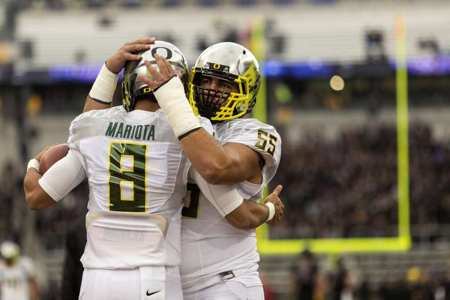 Oregon Ducks Marcus Mariota, left, and Hroniss Grasu, center, embrace during warm ups before a game against the Washington Huskies Saturday, Oct. 12, 2013, at Husky Stadium in Seattle. (Jordan Stead, seattlepi.com) Photo: JORDAN STEAD, SEATTLEPI.COM