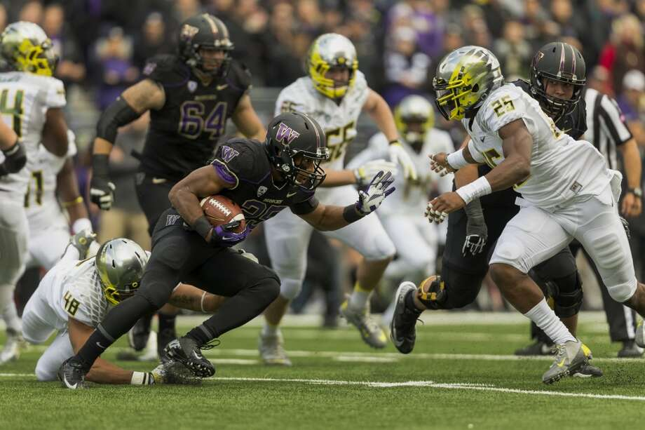 UW's Bishop Sankey, left, charges toward a wall of Duck defense during the first half of a game Saturday, Oct. 12, 2013, at Husky Stadium in Seattle. Ducks led the Huskies 21-7 at the half. The Oregon Ducks stand at 5-0 against the Washington Huskies, 4-1, so far in the season to date. (Jordan Stead, seattlepi.com) Photo: JORDAN STEAD, SEATTLEPI.COM