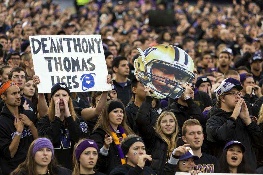 Fans hoist signs and player cutouts during the first half of a game Saturday, Oct. 12, 2013, at Husky Stadium in Seattle. Ducks led the Huskies 21-7 at the half. The Oregon Ducks stand at 5-0 against the Washington Huskies, 4-1, so far in the season to date. (Jordan Stead, seattlepi.com) Photo: JORDAN STEAD, SEATTLEPI.COM