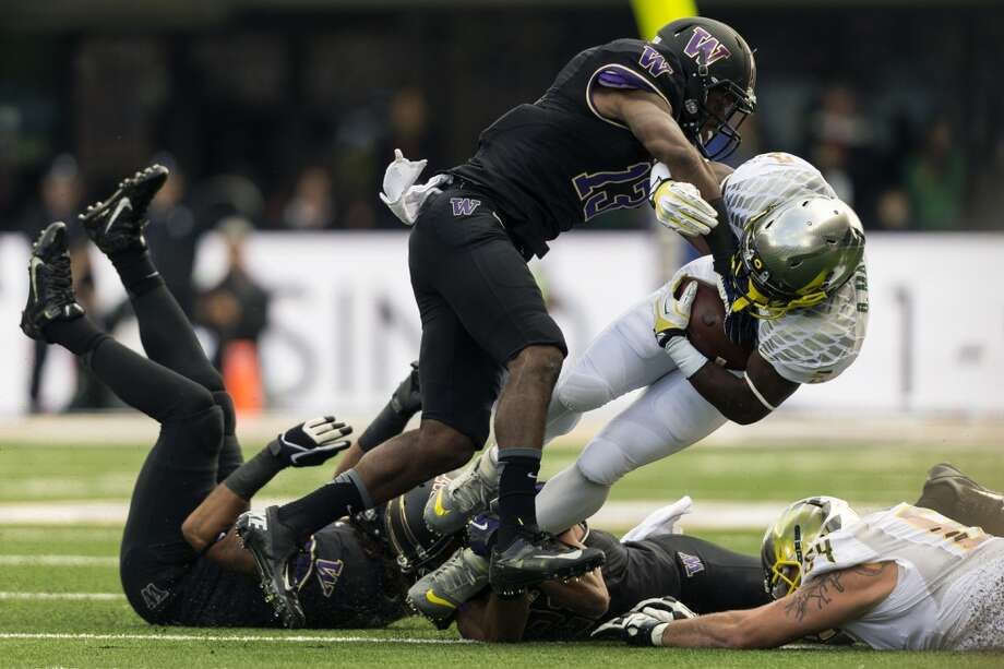 UW's Will Shamburger, left, tackles Oregon's Bralon Marshall, right, during the first half of a game Saturday, Oct. 12, 2013, at Husky Stadium in Seattle. Ducks led the Huskies 21-7 at the half. The Oregon Ducks stand at 5-0 against the Washington Huskies, 4-1, so far in the season to date. (Jordan Stead, seattlepi.com) Photo: JORDAN STEAD, SEATTLEPI.COM