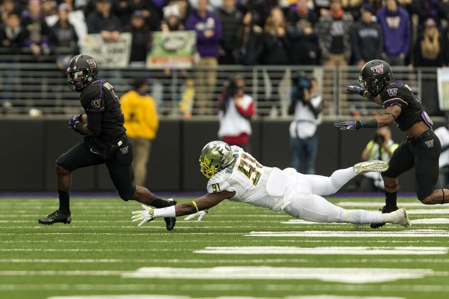 Oregon's Tony Washington, center, misses a tackle on a dive during the first half of a game Saturday, Oct. 12, 2013, at Husky Stadium in Seattle. Ducks led the Huskies 21-7 at the half. The Oregon Ducks stand at 5-0 against the Washington Huskies, 4-1, so far in the season to date. (Jordan Stead, seattlepi.com) Photo: JORDAN STEAD, SEATTLEPI.COM