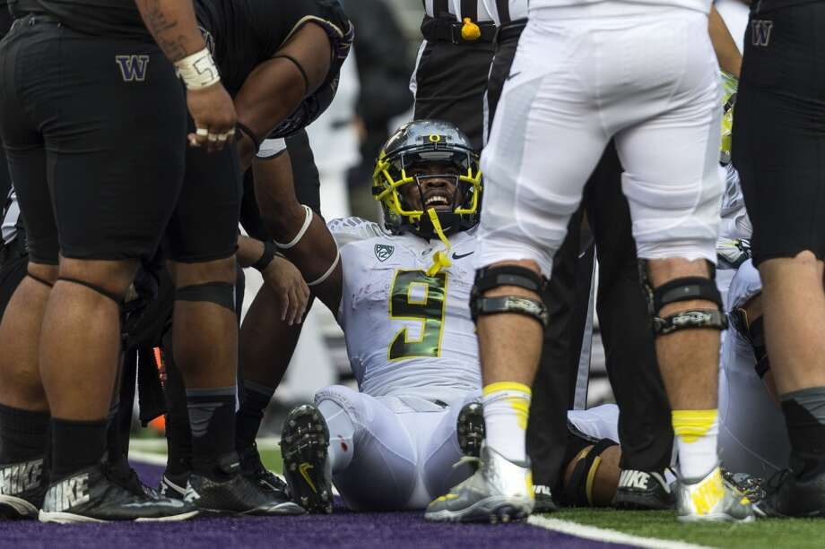Oregon's Arik Armstead, center, reacts to hearing of a touchdown for his team after emerging from under a pile of players during the first half of a game Saturday, Oct. 12, 2013, at Husky Stadium in Seattle. Ducks led the Huskies 21-7 at the half. The Oregon Ducks stand at 5-0 against the Washington Huskies, 4-1, so far in the season to date. (Jordan Stead, seattlepi.com) Photo: JORDAN STEAD, SEATTLEPI.COM