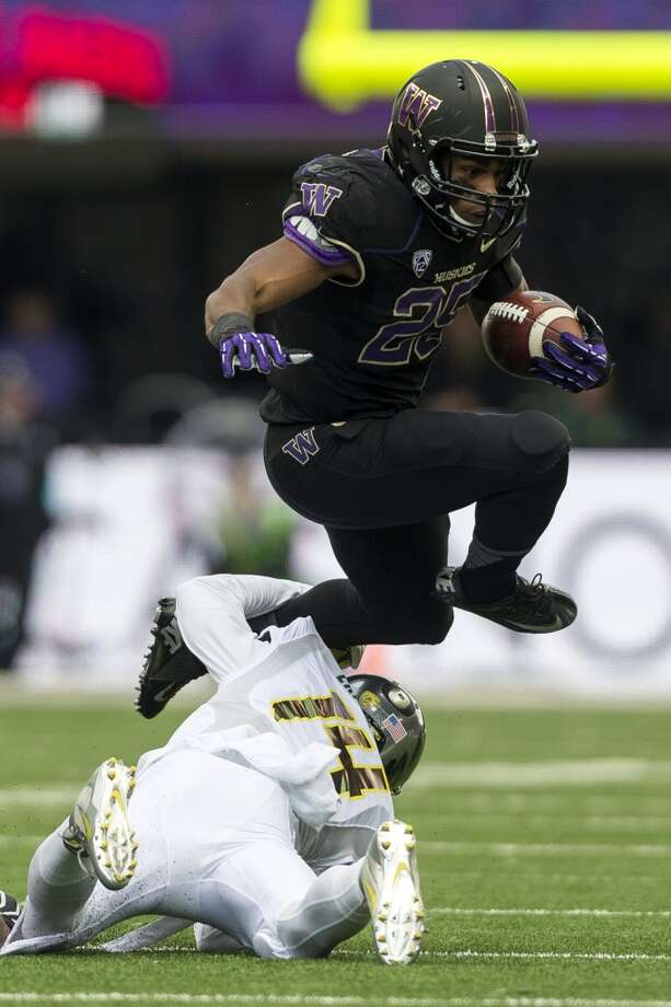 UW's Bishop Sankey, top, leaps over Oregon's Ifo Ekpre-Olomu during the first half of a game Saturday, Oct. 12, 2013, at Husky Stadium in Seattle. Ducks led the Huskies 21-7 at the half. The Oregon Ducks stand at 5-0 against the Washington Huskies, 4-1, so far in the season to date. (Jordan Stead, seattlepi.com) Photo: JORDAN STEAD, SEATTLEPI.COM