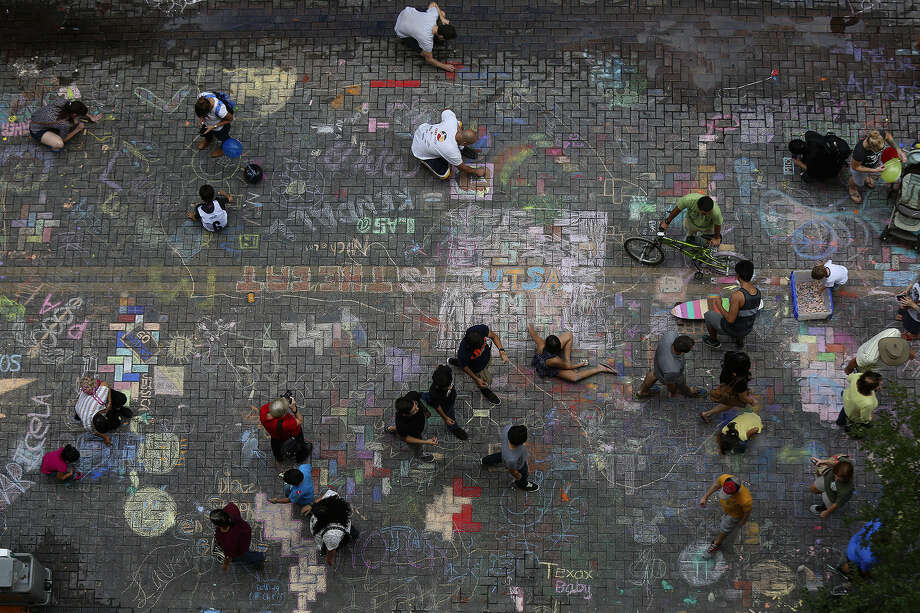 People walk and draw in the freestyle section of Chalk It Up on Houston Street in downtown San Antonio. Photo: Photos By Lisa Krantz / San Antonio Express-News