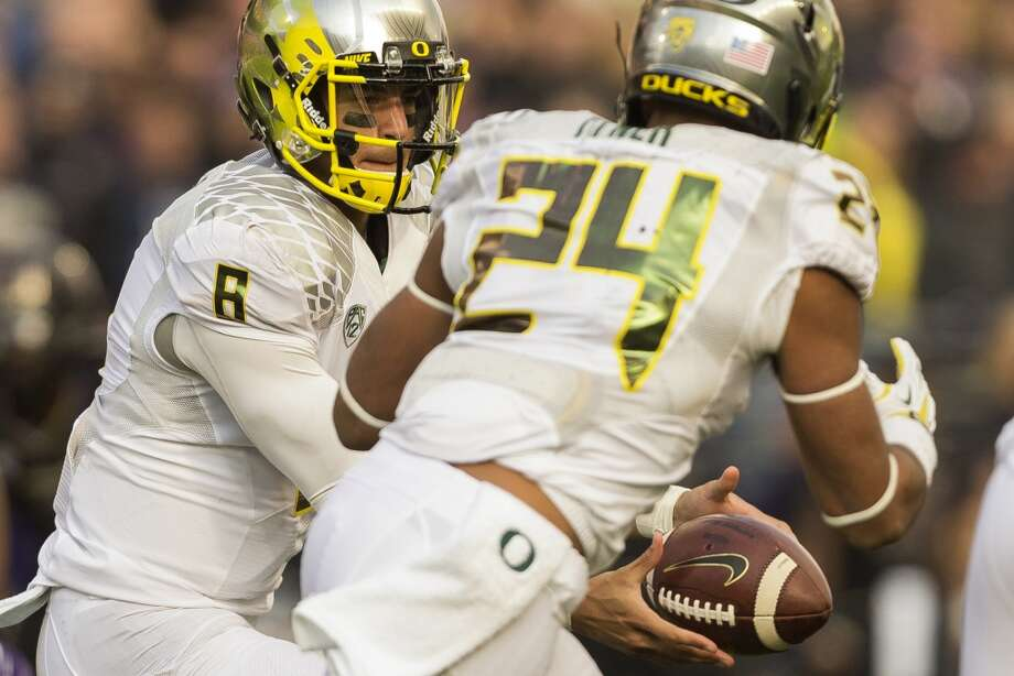 Oregon's quarterback Marcus Mariota, left, hands off during the second half of a game Saturday, Oct. 12, 2013, at Husky Stadium in Seattle. The Ducks beat the Huskies 45-24. (Jordan Stead, seattlepi.com) Photo: JORDAN STEAD, SEATTLEPI.COM