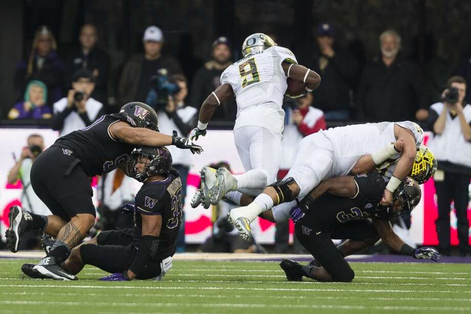 Oregon's Bralon Marshall, center, sails between two tackles during the second half of a game Saturday, Oct. 12, 2013, at Husky Stadium in Seattle. The Ducks beat the Huskies 45-24. (Jordan Stead, seattlepi.com) Photo: JORDAN STEAD, SEATTLEPI.COM