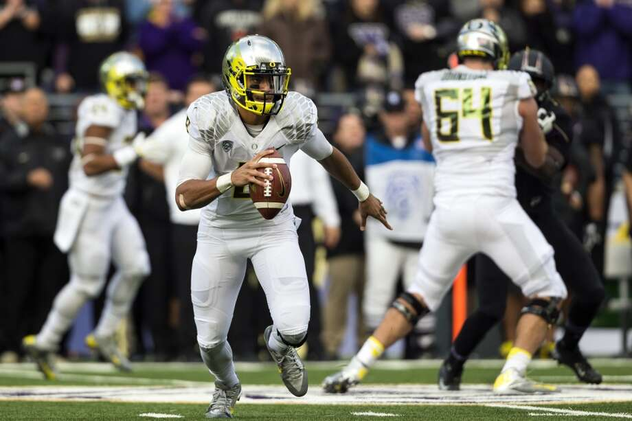 Oregon's quarterback Marcus Mariota, center left, looks for a pass during the second half of a game Saturday, Oct. 12, 2013, at Husky Stadium in Seattle. The Ducks beat the Huskies 45-24. (Jordan Stead, seattlepi.com) Photo: JORDAN STEAD, SEATTLEPI.COM