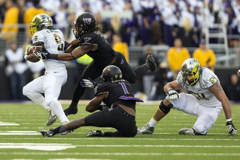 Oregon's Bralon Marshall, left, is tackled during the second half of a game Saturday, Oct. 12, 2013, at Husky Stadium in Seattle. The Ducks beat the Huskies 45-24. (Jordan Stead, seattlepi.com) Photo: JORDAN STEAD, SEATTLEPI.COM