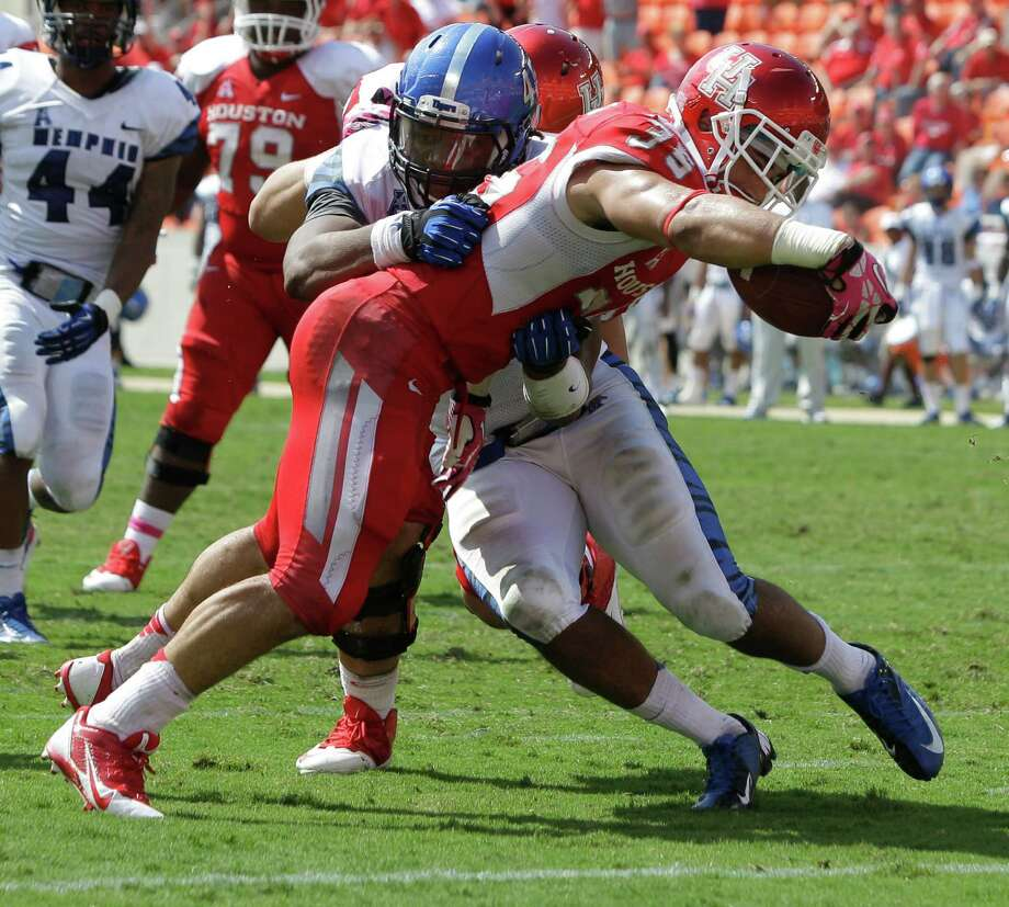 Kenneth Farrow muscles his way past Memphis' Anthony Brown to score on a 6-yard run to give UH some breathing room in the fourth quarter. Photo: Melissa Phillip, Staff / © 2013  Houston Chronicle